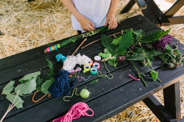 A pile of large leaves and craft materials on a wooden table outside