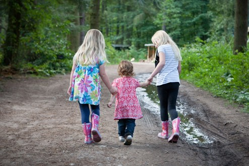 Three children walking one a forest path