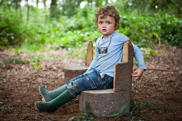 A child sitting on a wooden seat carved out of a log