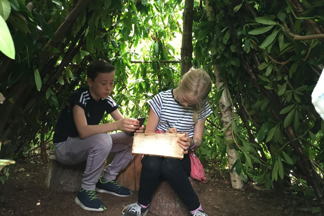 Two children drawing in a shelter made from branches