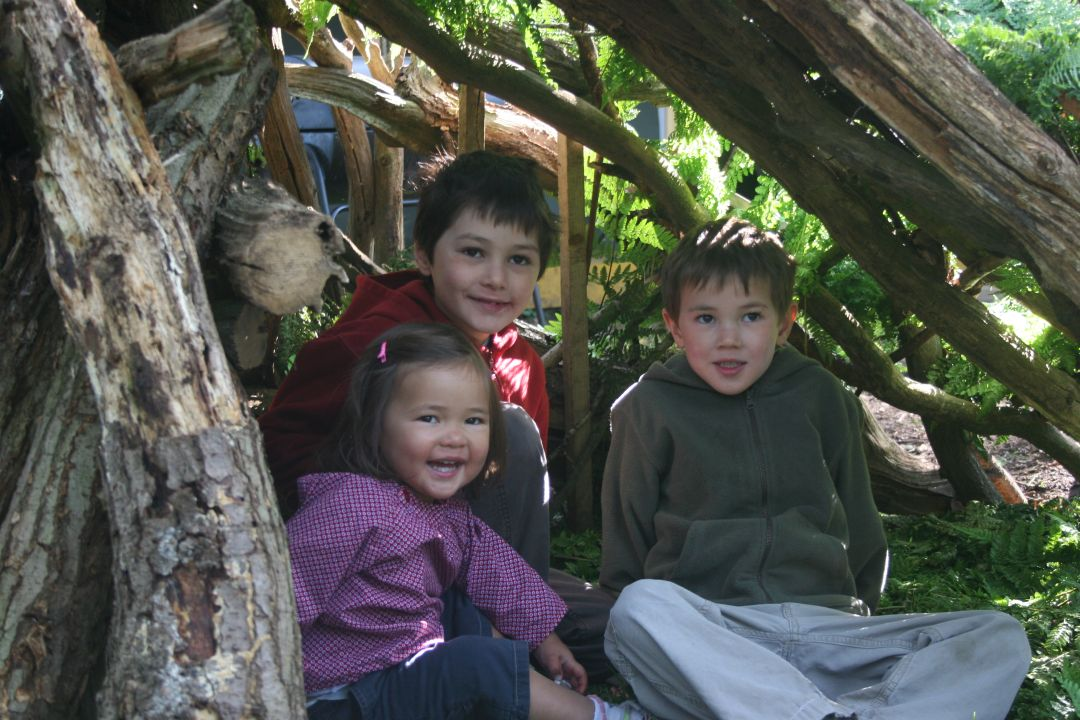 Three children sitting inside a shelter made from logs and branches