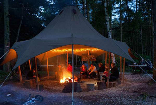 A large awning over a seating area and campfire