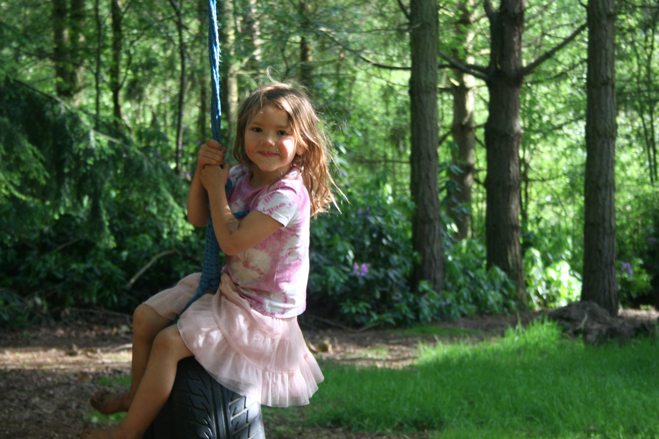 A child on a tyre swing in woodland